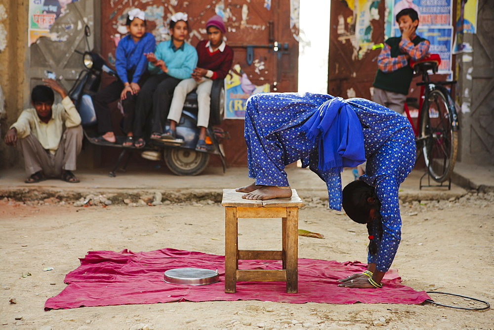 Professional contortionist street performer doing yoga tricks on side of road, Pinjore, Punjab, India, Asia - 734-227