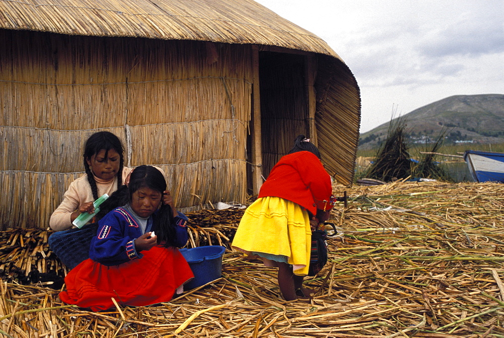 Small group of women and girls of the Uros people on the floating reed islands, Lake Titicaca, Peru, South America