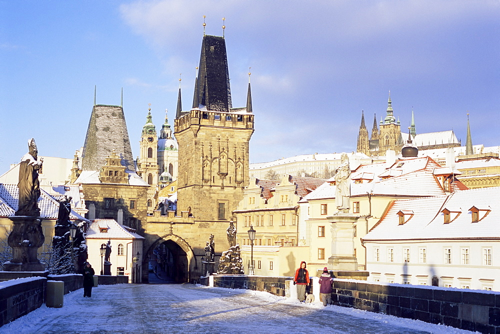 Snow-covered Gothic Charles bridge with Baroque statues, Romanesque and Gothic Malostranske bridge towers and Prague castle, Mala Strana, Prague, Czech Republic, Europe