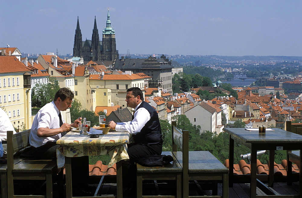 Two men having lunch outdoors while enjoying the view of Prague Castle from the Restaurant Ozivle drevo, Hradcany, Prague, Czech Republic, Europe