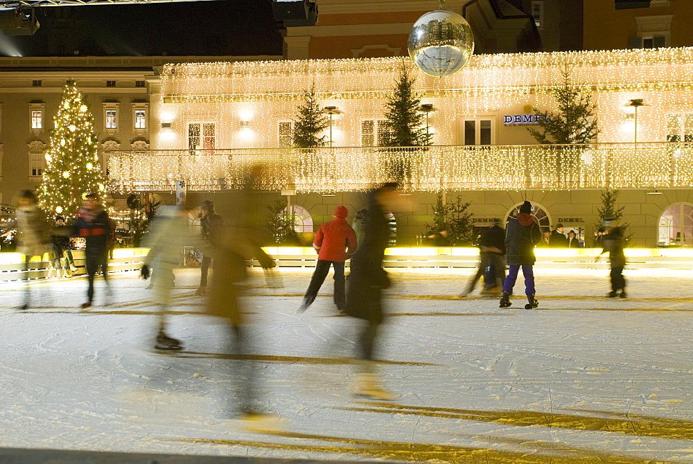 Ice skating at night on ice rink at Mozartplatz square, Salzburg, Austria, Europe
