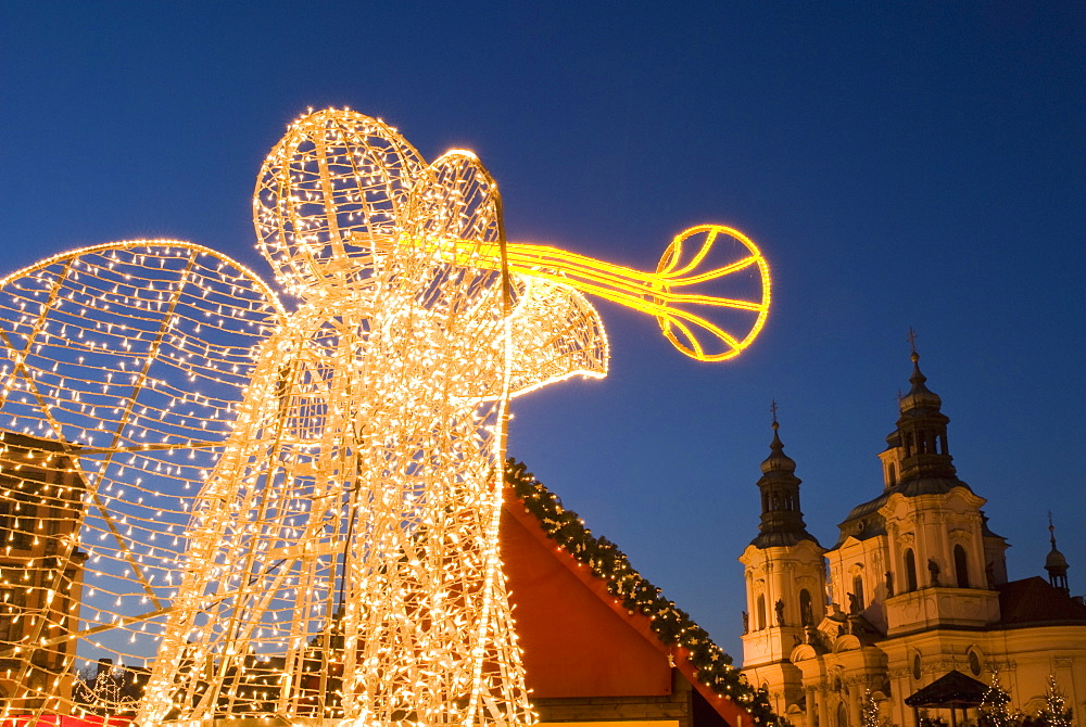 Glowing angel, part of Christmas decoration at Staromestske (Old Town Square) with Baroque St. Nicholas church at twilight, Stare Mesto, UNESCO World Heritage Site, Prague, Czech Republic, Europe
