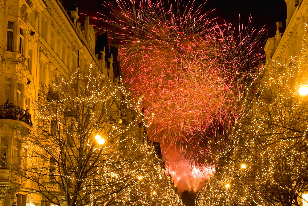 Christmas lights on trees and 19th century houses along Parizska Street and New Years Day fireworks, Stare Mesto (Old Town), UNESCO World Heritage Site, Prague, Czech Republic, Europe