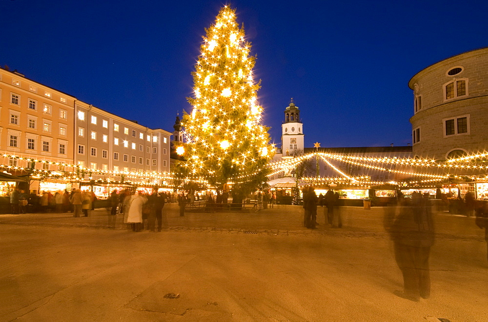 Christmas tree and stalls of historical Salzburg Christkindlmarkt (Christmas market) with Glockenspiel building, Residenzplatz at twilight, Salzburg, Austria, Europe