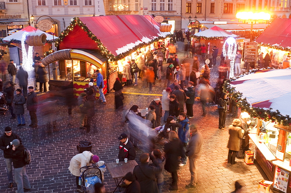 Stalls and people at Christmas Market at dusk, Old Town Square, Stare Mesto, Prague, Czech Republic, Europe