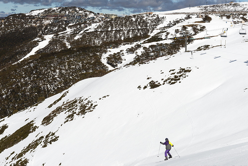 Young skier skiing down The Chute and Mount Hotham Village, Mount Hotham, Victoria, Australia, Pacific - 737-713