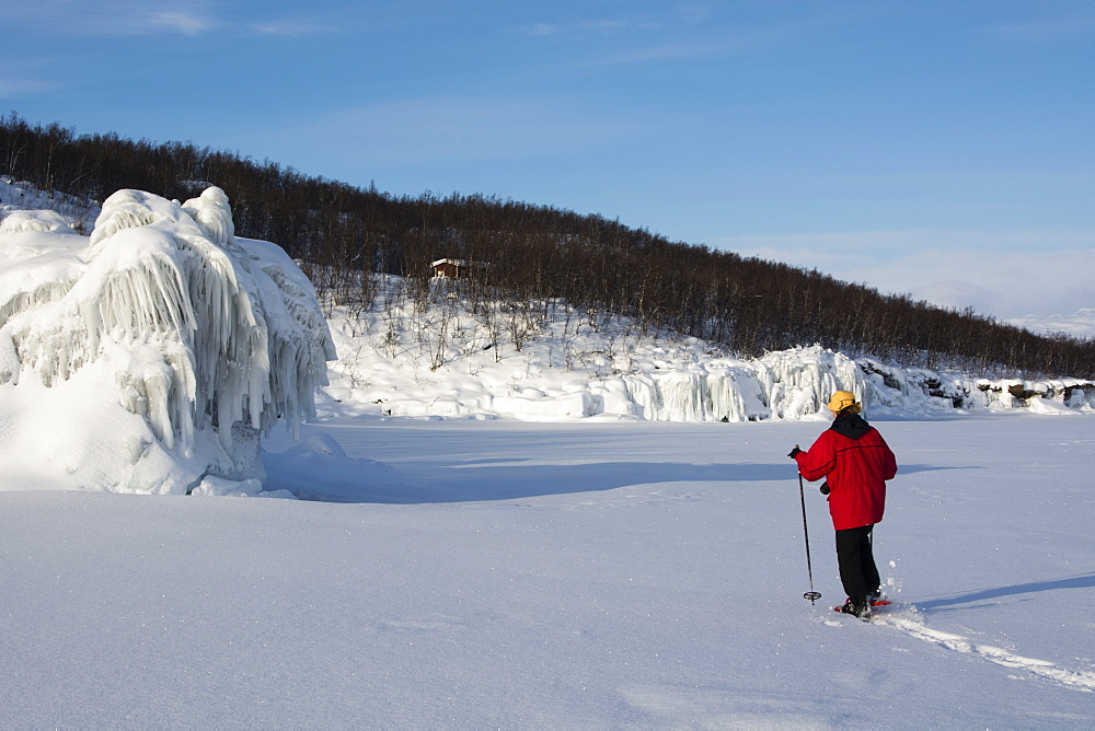 A woman walking across frozen Tornetrask Lake, Abisko National Park, Sweden.