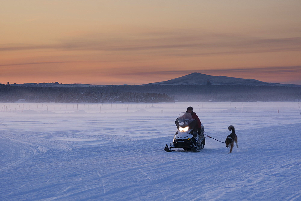 A snow mobile crossing the frozen river Torne at sunset, Jukkasjarvi, Sweden.