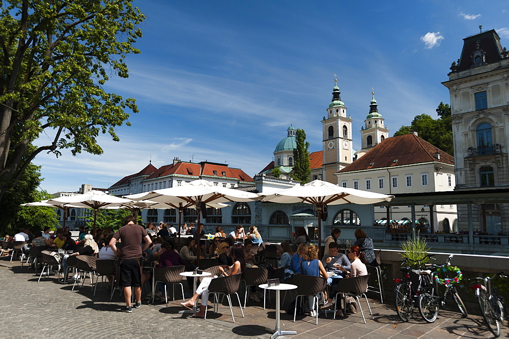 Outdoor cafes along the Ljubljanica river and the cathedral of Saint Nicholas in the background, Ljubljana, Slovenia. - 741-5466