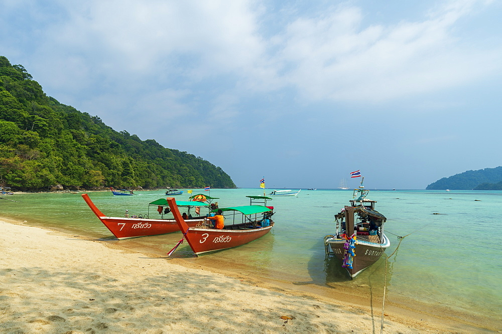 Three long tailed boats on a sandy beach.