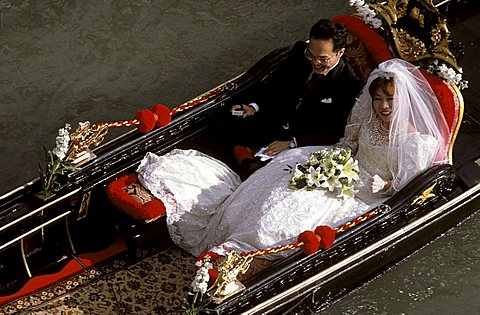 Newlywed couple on gondola, Venice, Veneto, Italy