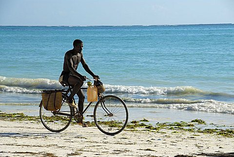 A man riding his bicycle on the beach, Zanzibar, United Republic of Tanzania, Africa
