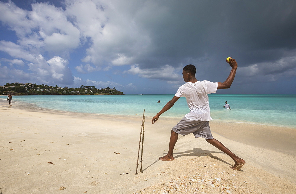 Kids playing on the beach surrounded by the turquoise Caribbean sea The Nest, Antigua and Barbuda, Leeward Islands, West Indies
