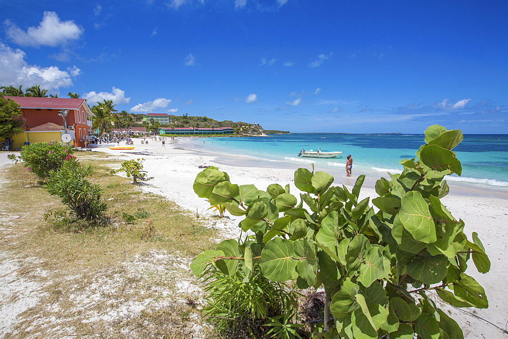 White sand and tourists frame the turquoise Caribbean sea at Long Bay Beach, Antigua and Barbuda, Leeward Islands, West Indies