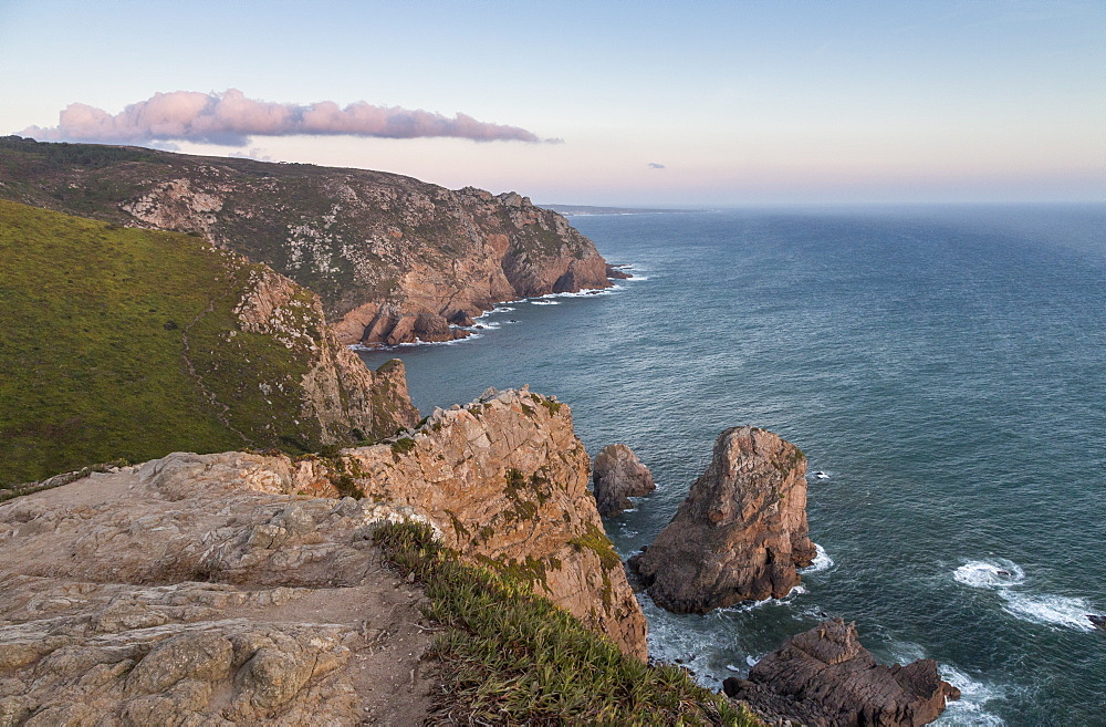 Ocean waves crashing on the cliffs of the Cabo da Roca cape at sunset, Sintra, Portugal, Europe