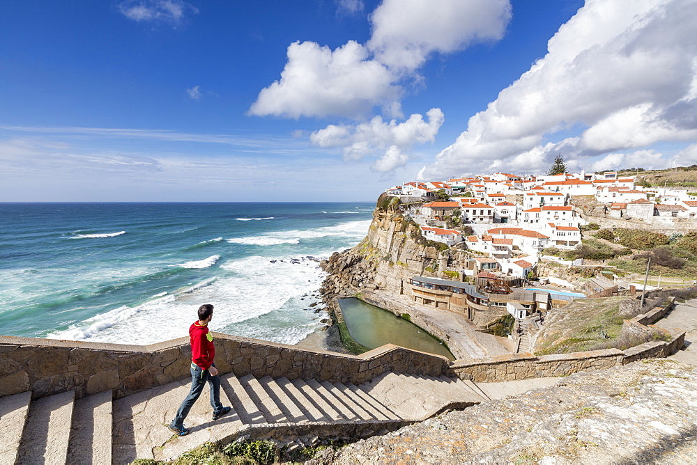 Tourist admires the perched village of Azenhas do Mar surrounded by the blue water of the Atlantic Ocean, Sintra, Portugal, Europe