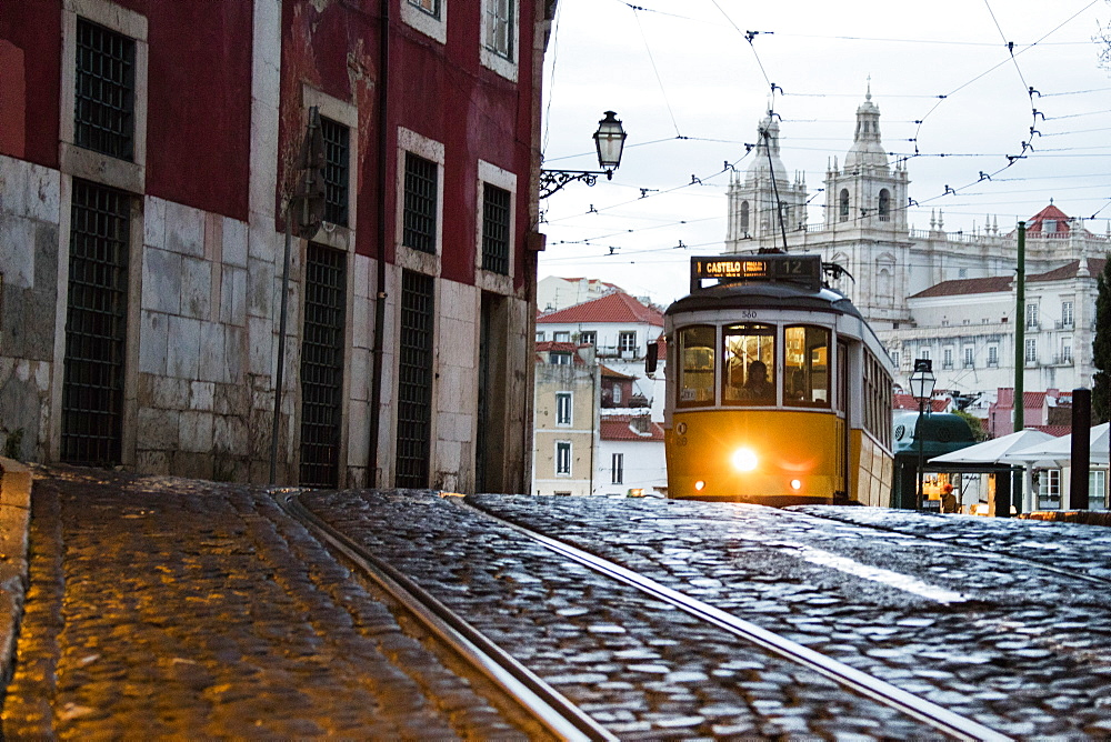 Romantic atmosphere in the old streets of Alfama with the castle in the background and tram number 28, Alfama, Lisbon, Portugal, Europe