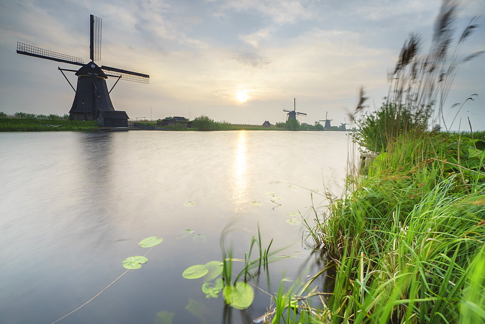 Morning sun just risen shines in the canal where windmills are reflected Kinderdijk, Rotterdam, South Holland, Netherlands, Europe