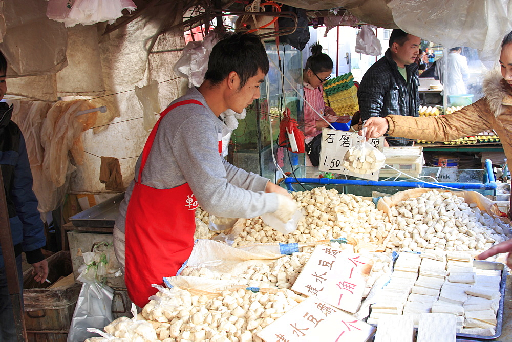 Man selling different varieties of tofu in a market in Kunming, China