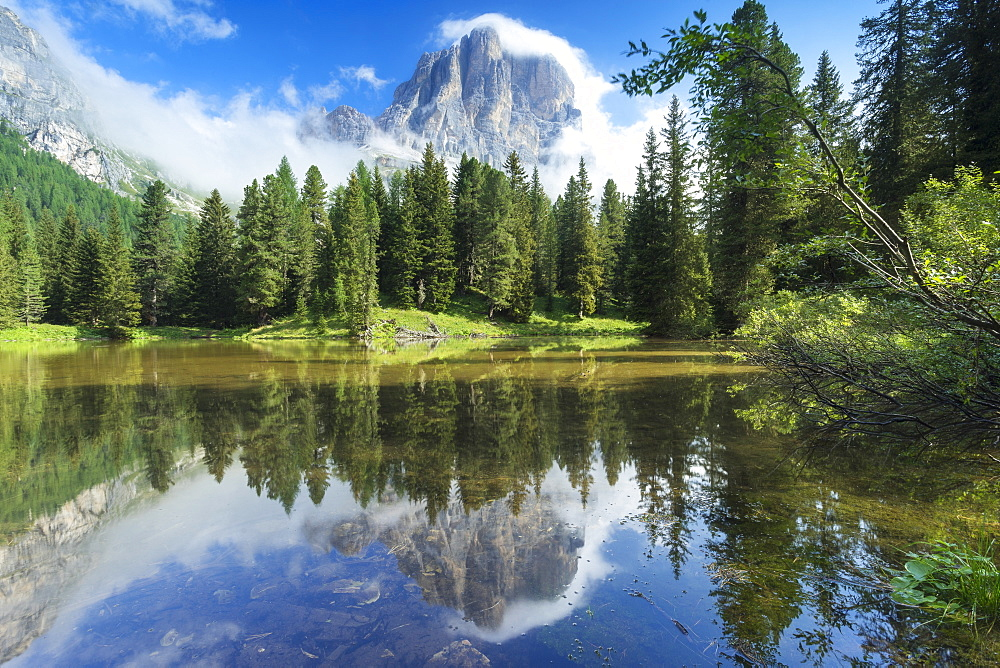 The lake Bai de Dones reflects with Tofana di Rozes sorrunded by clouds, Falzarego Pass, Veneto, Italy, Europe