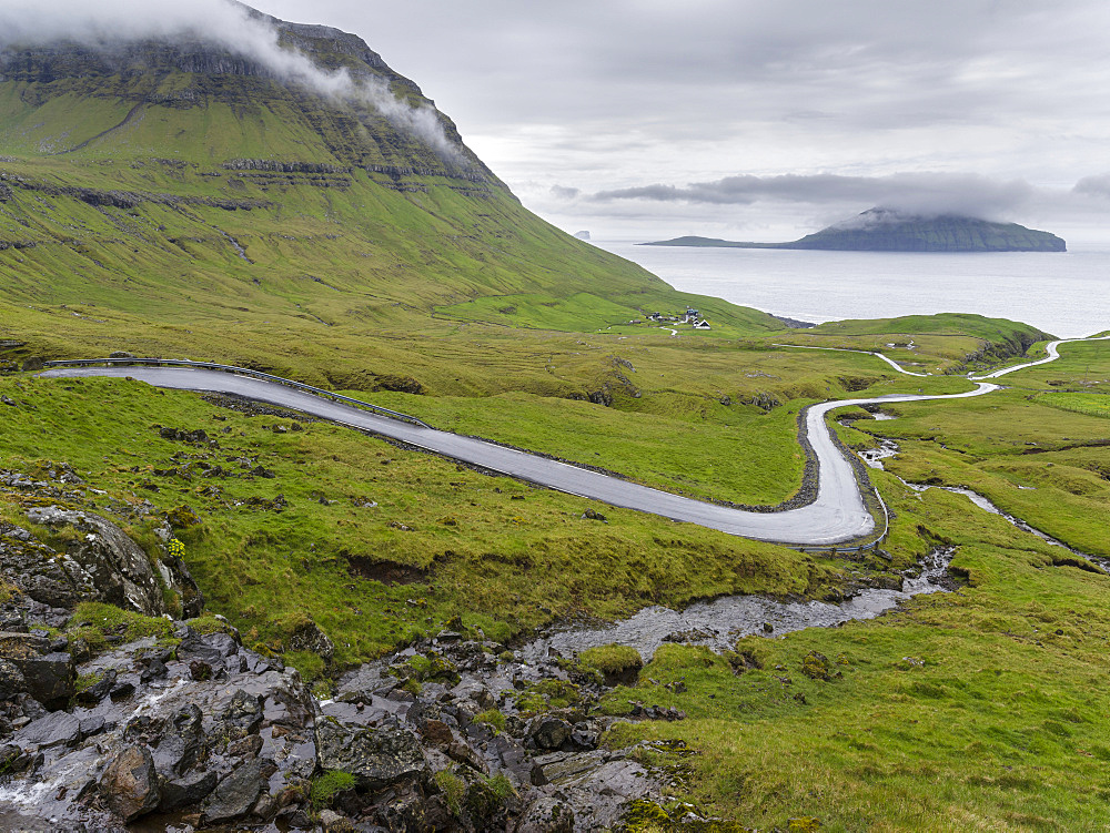Mountain road to the  Nordradalur at the west coast. Koltur island in the background.  The island Streymoy, one of the two large islands of the Faroe Islands  in the North Atlantic.  Europe, Northern Europe, Denmark, Faroe Islands - 746-88072