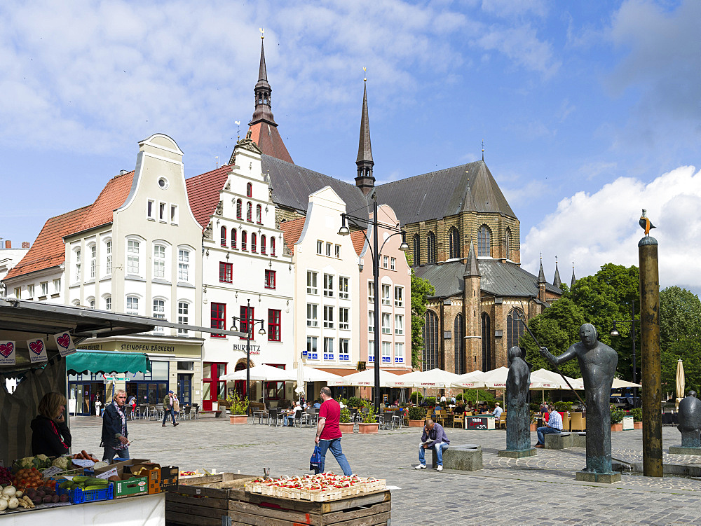 Traditional houses buildt in the middle ages at the  Neuer Markt (new market) and church Marienkirche in the background. The hanseatic city of Rostock at the coast of the german baltic sea.  Europe,Germany, Mecklenburg-Western Pomerania, June