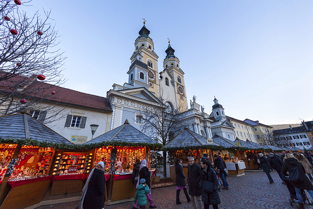The Christmas Market in Brixen (also called  Bressanone or Persenon) on the medieval market place Europe, the steeples of Brixen cathedral in the background. Europe, Central Europe, Italy, South Tyrol, December