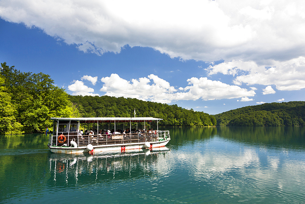 The Plitvice Lakes in the National Park Plitvicka Jezera in Croatia. Visitors taking a cruise on lake Kozjak.  The Plitvice Lakes are a string of lakes connected by waterfalls. They are in a valley, which becomes a canyon in the lower parts of the National Park. The waterfalls are formed mostly by travertine (tufa) barriers between the lakes. The lakes are listed as  UNESCO World heritage and are visited by close to one million tourists per year. Europe, South Eastern Europe, Croatia
