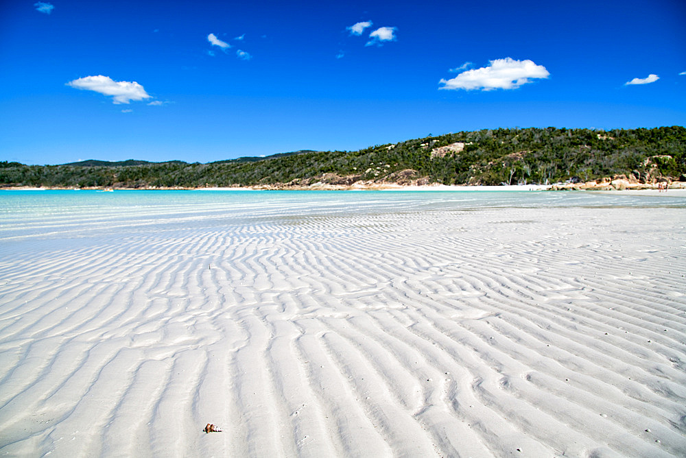 Crystal clear water on a wonderful beach. Shallow ocean water with island view.