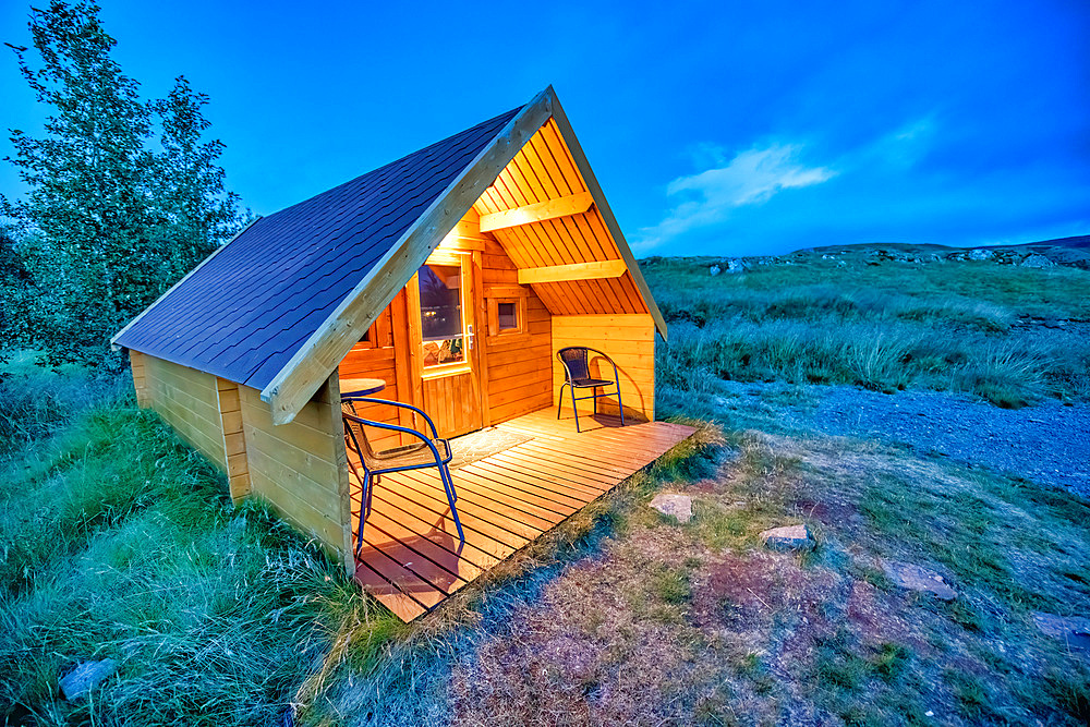 Beautiful chalet isolated in the mountains at sunset. Wooden front with chairs