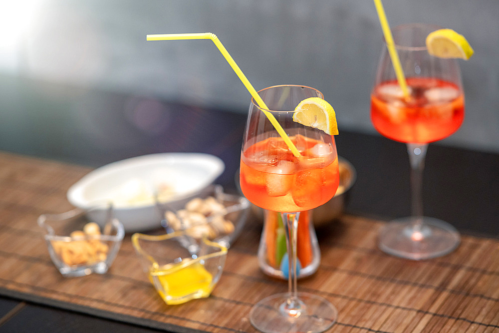 Closeup of some glasses with cocktails with straws and nuts on a brown table.