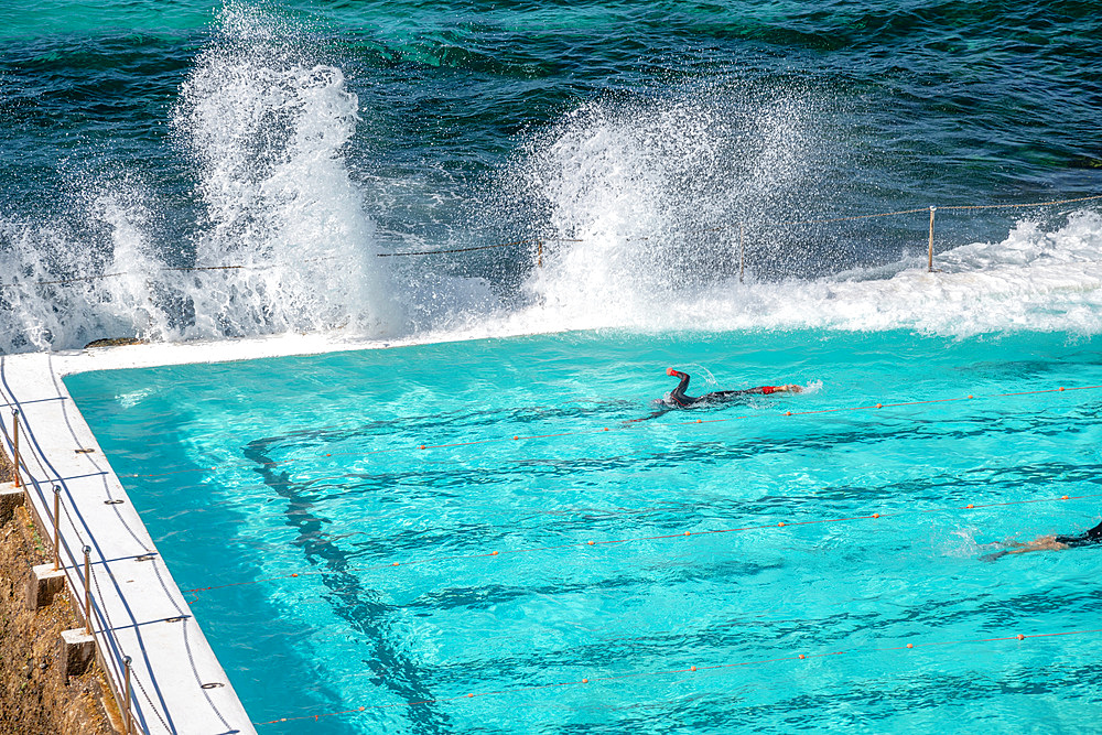 Swimmers enjoy beautiful pool along the sea.