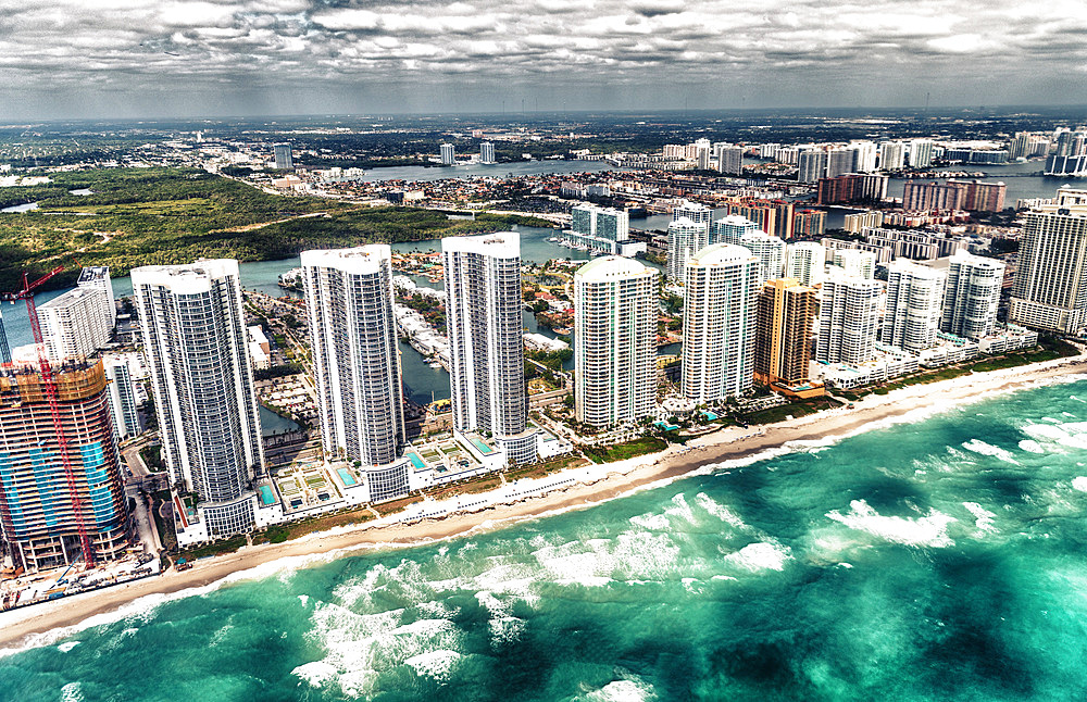 Aerial view of North Miami Beach skyscrapers with sun and clouds.