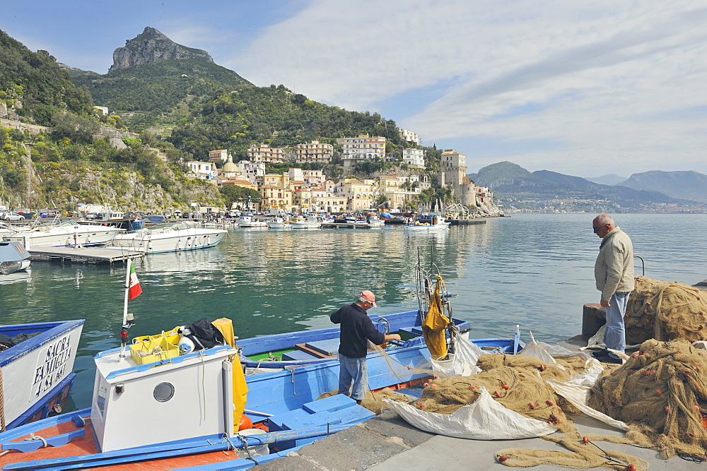 Two fishermen returning from the sea gather their nets in the harbour of Cetara, Amalfi Coast, Campania, Italy.