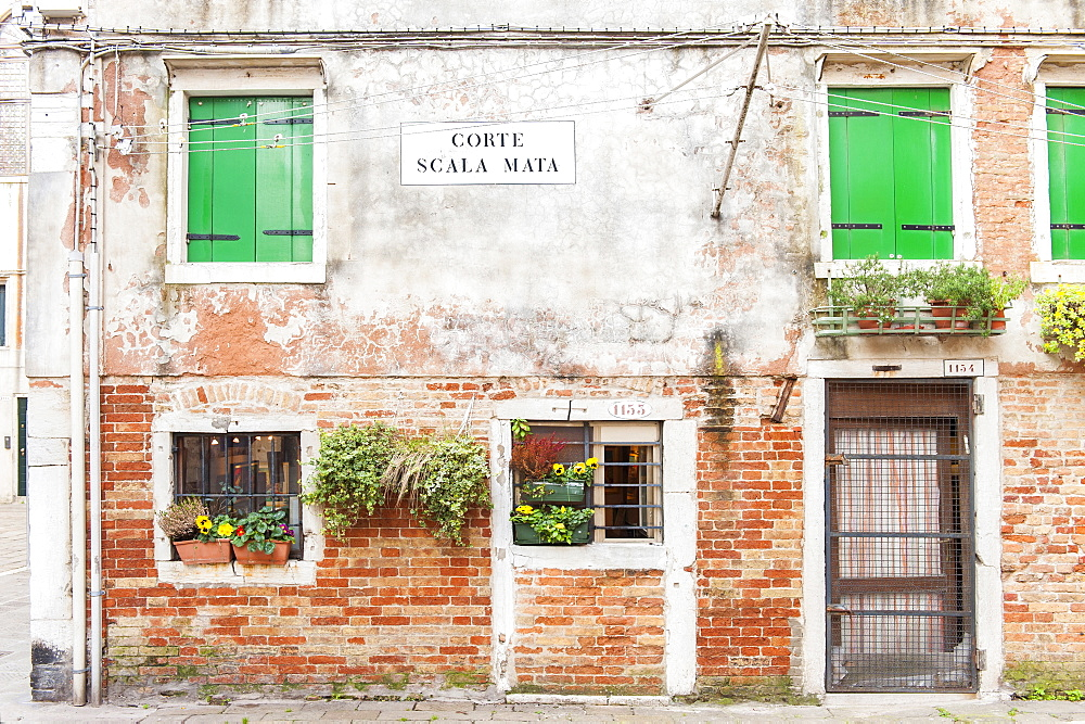 The front of an old house in Corte Scala Mata square, Cannaregio sestiere, not far from the Jewish ghetto in Venice, Veneto, Italy, Europe