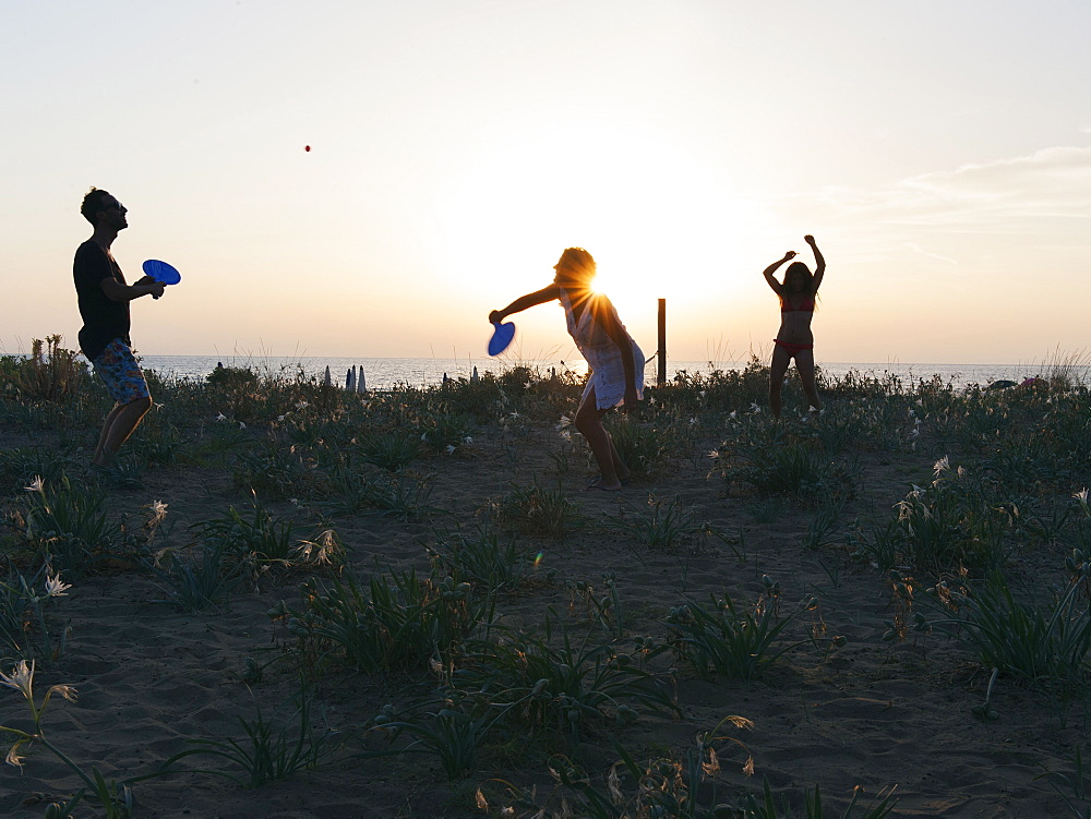 Boys playing racket ball at sunset on the beach, EcoVillage Maremirtilli, Capaccio Paestum, Campania, Italy, Europe