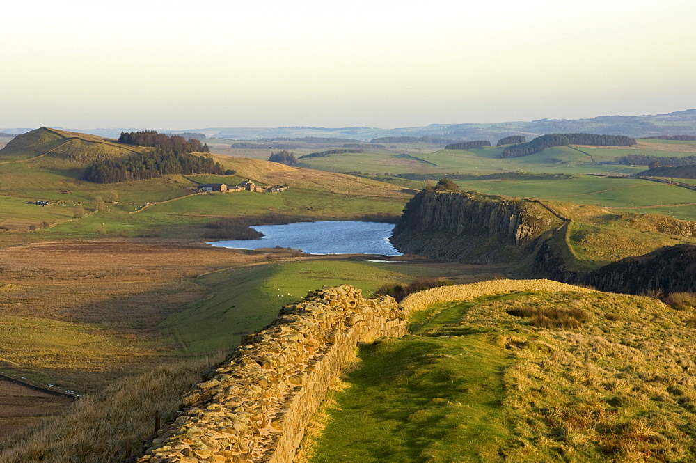 Towards sunset, view east along Hadrians Wall from Windshields Crag to Crag Lough and Hotbank Farm, UNESCO World Heritage Site, Northumberland National Park, Northumbria, England, United Kingdom, Europe