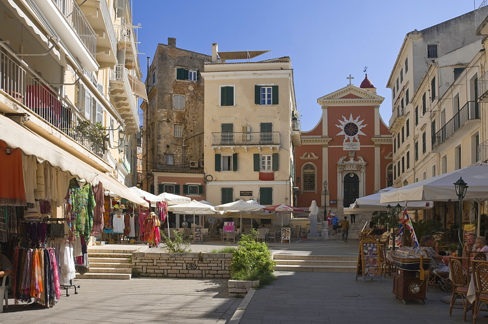 A sunny square with a church, pavement cafes, and small shops, in old Corfu. Island of Corfu, Ionian Islands, Greek Islands, Greece, Europe