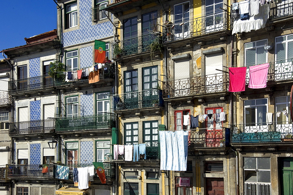 A residential street in the old town with traditional wrought iron balconies, blue and white tiled panels on the outside walls, washing hanging in the sun, Oporto, Portiugal, Europe