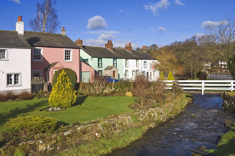 Pastel coloured cottages alongside the beck in Calthwaite, John Peel Country, Cumbria, England, United Kingdom, Europe