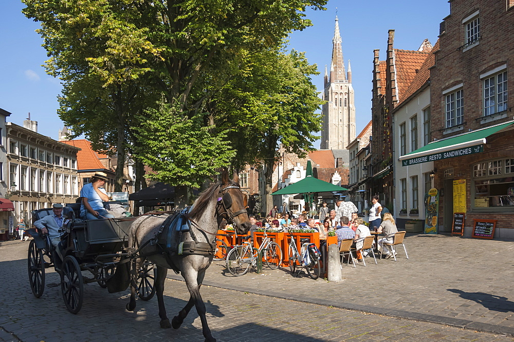 Square with cafe, horse and carriage, and spire of Church of Our Lady, Bruges, Belgium, Europe