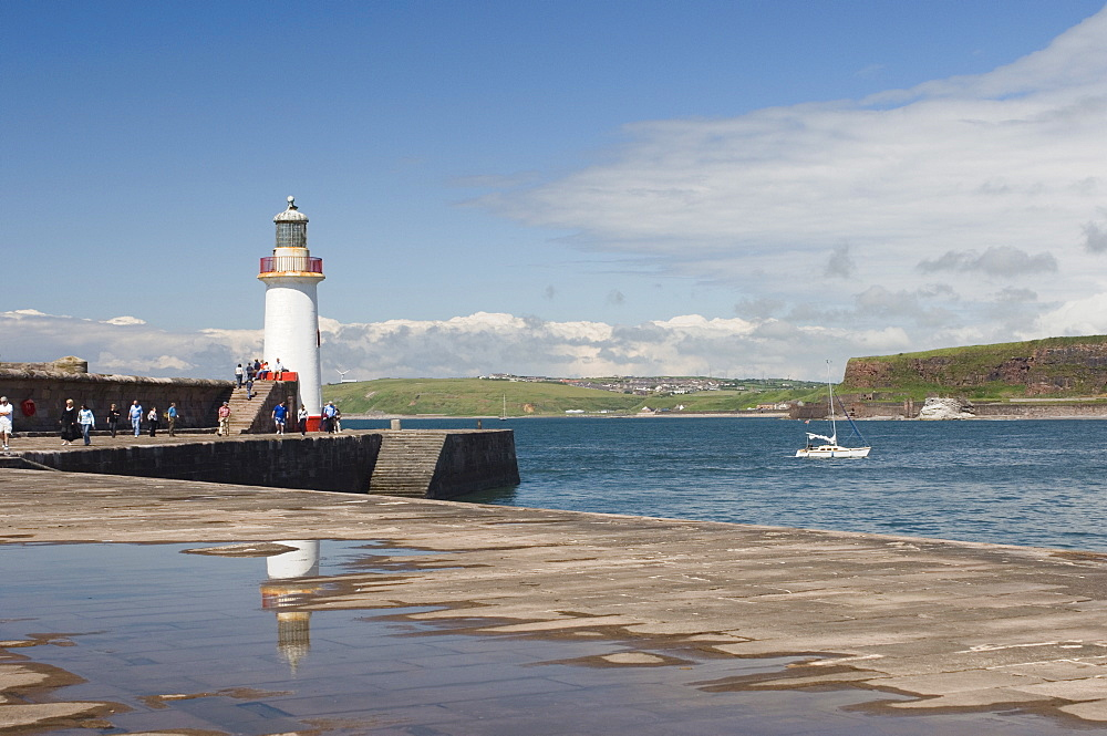 Lighthouse at entrance to outer harbour, motor yacht entering, Whitehaven, Cumbria, England, United Kingdom, Europe