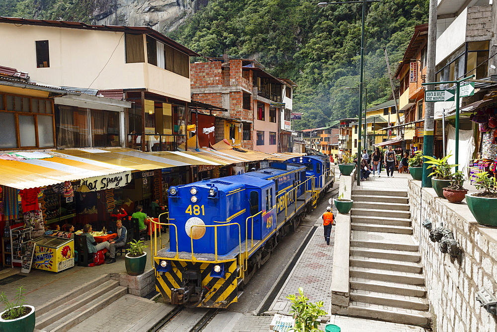 Train crossing the town of Aguas Calientes, Peru, South America