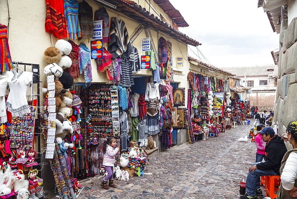 Shops along the the Inca wall at Hathunrumiyoq Street, las piedras del los 12 angulos (the stone of the 12 angles), Cuzco, Peru, South America