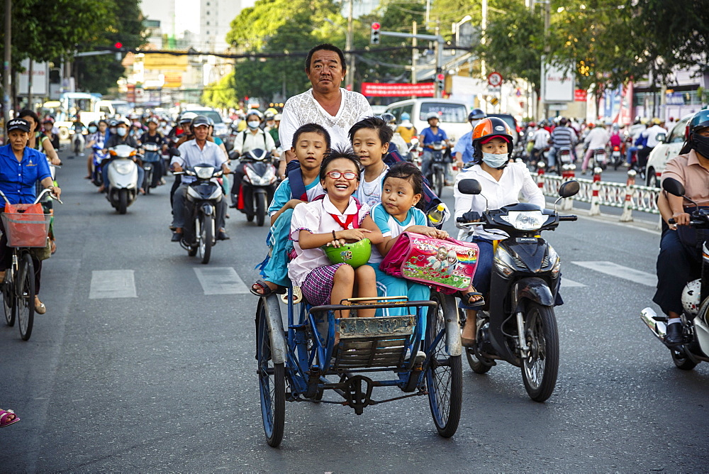 School kids riding a cyclo on a busy street, Ho Chi Minh City (Saigon), Vietnam, Indochina, Southeast Asia, Asia