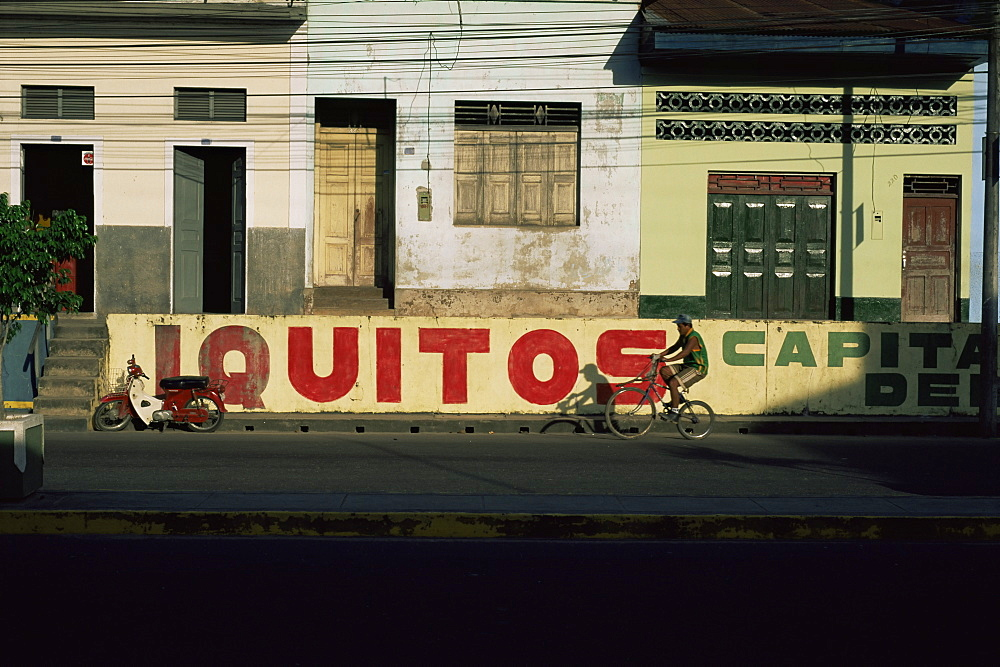 Bicycle cruises past homes, Iquitos, Peru, South America