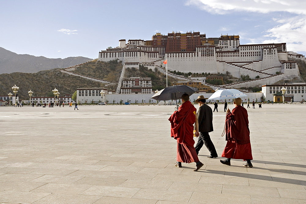 Monks carrying umbrellas to shield against the sun, in front of the Potala Palace, UNESCO World Heritage Site, Lhasa, Tibet, China, Asia