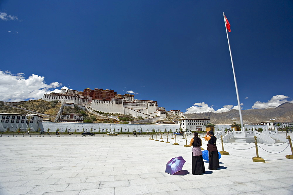 Two Tibetan women praying, in front of the Potala Palace, UNESCO World Heritage Site, with Chinese flag to the right, Lhasa, Tibet, China, Asia