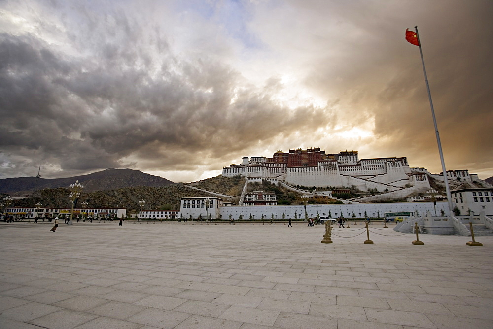 The red flag of China flying in Potala Square on a stormy afternoon in front of the Potala Palace, UNESCO World Heritage Site, Lhasa, Tibet, China, Asia