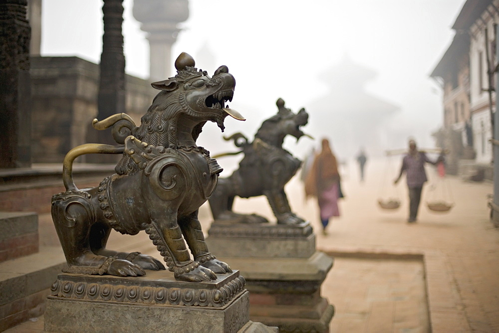 Durbar Square, Bhaktapur, Kathmandu valley, Nepal. Guardian lions on the steps of a temple. Foggy winter morning November 2005.